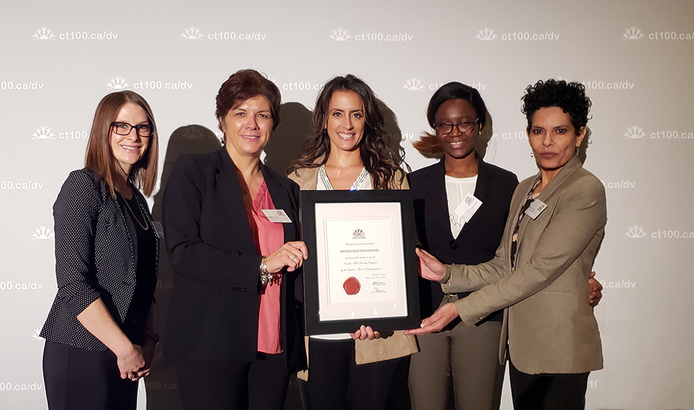 employees posing with award