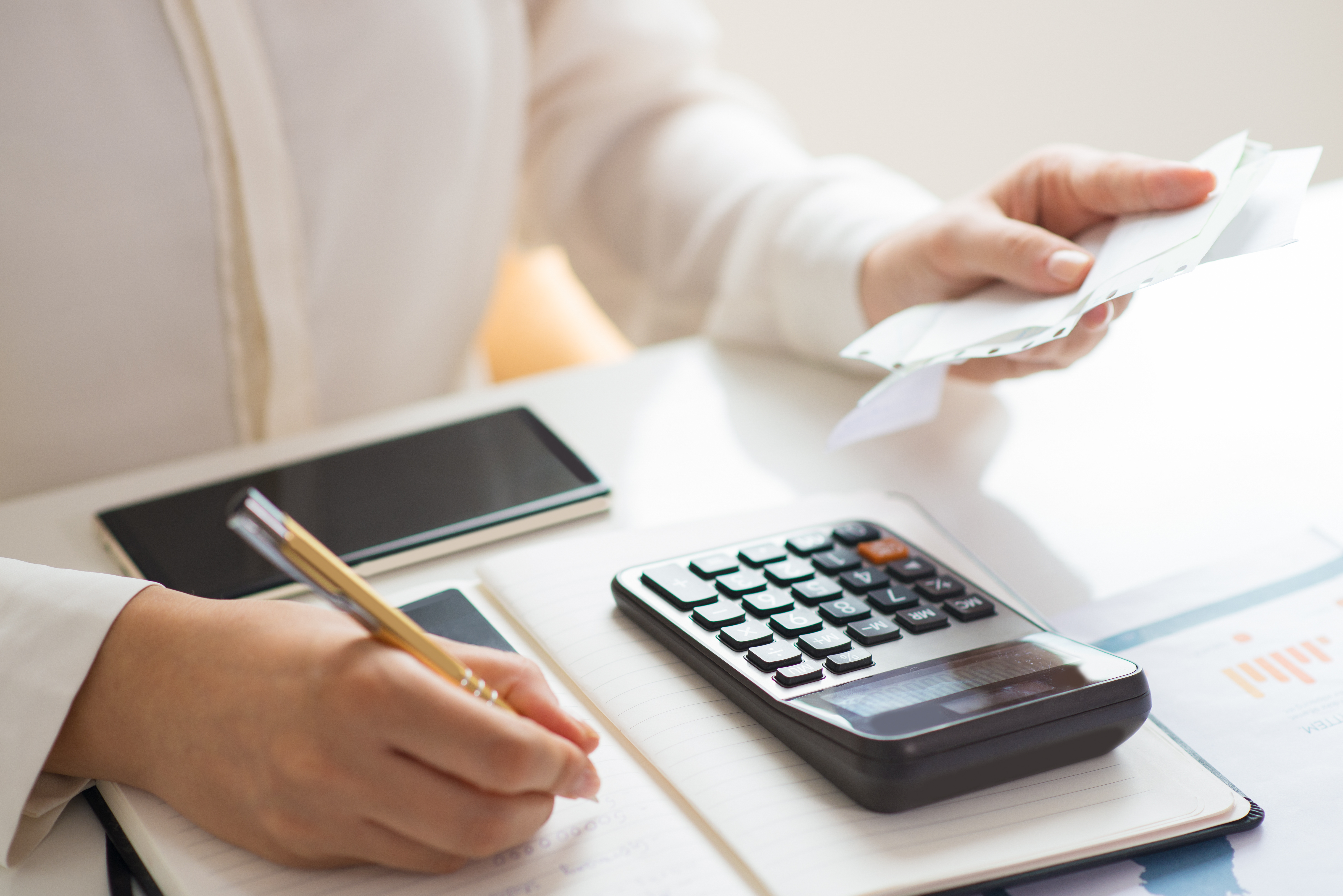 Closeup of person holding bills and calculating them.