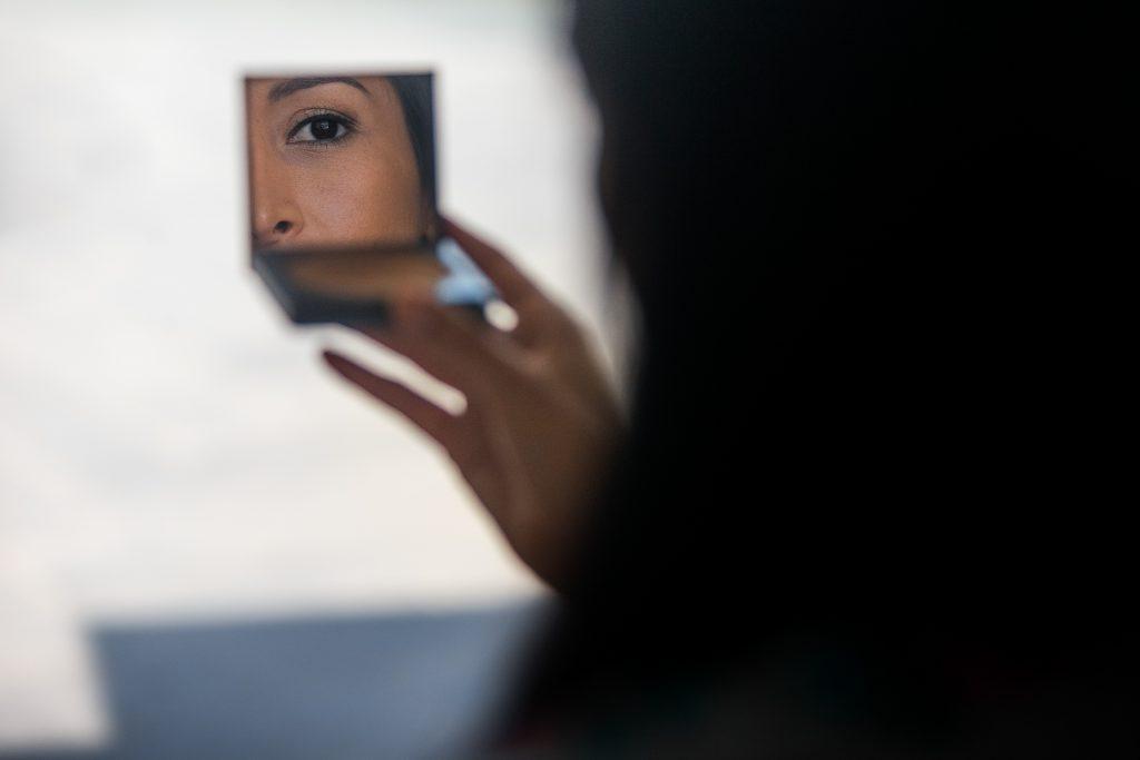 Woman looks in little mirror of her powder