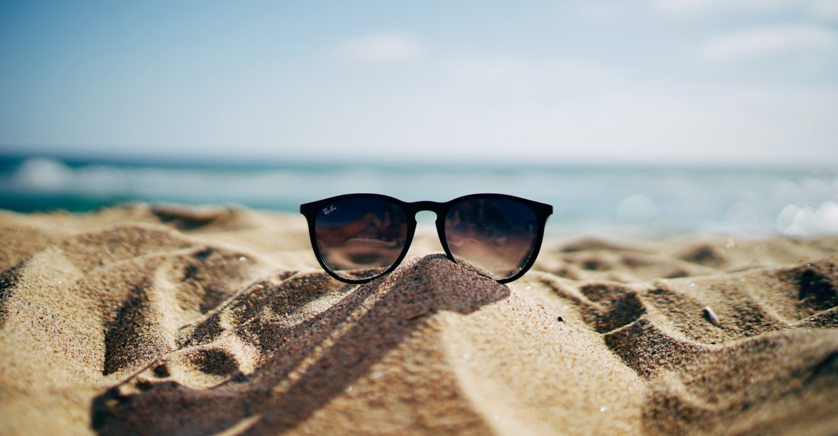sunglasses on sand at beach